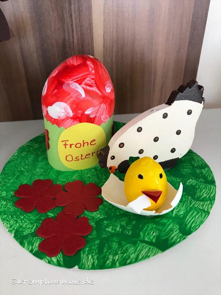 Rot-weißes Osterei mit Henne und Küken auf Blumenwiese