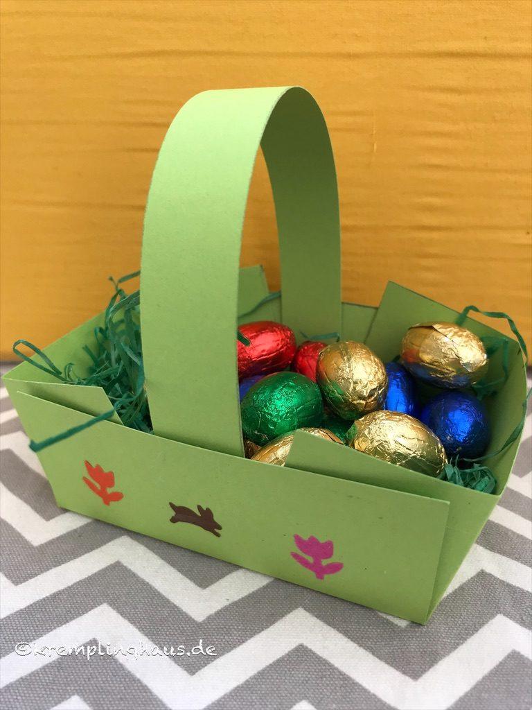 grüner Osterkorb aus Papier mit Schokoeiern