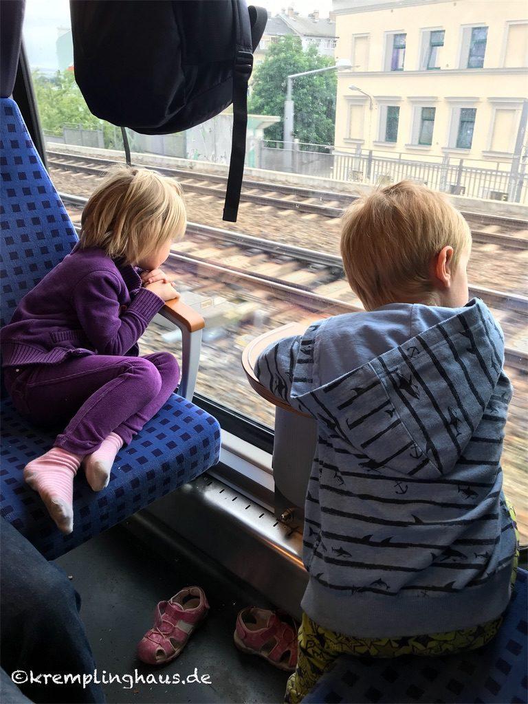Kinder schauen in Zug aus dem Fenster