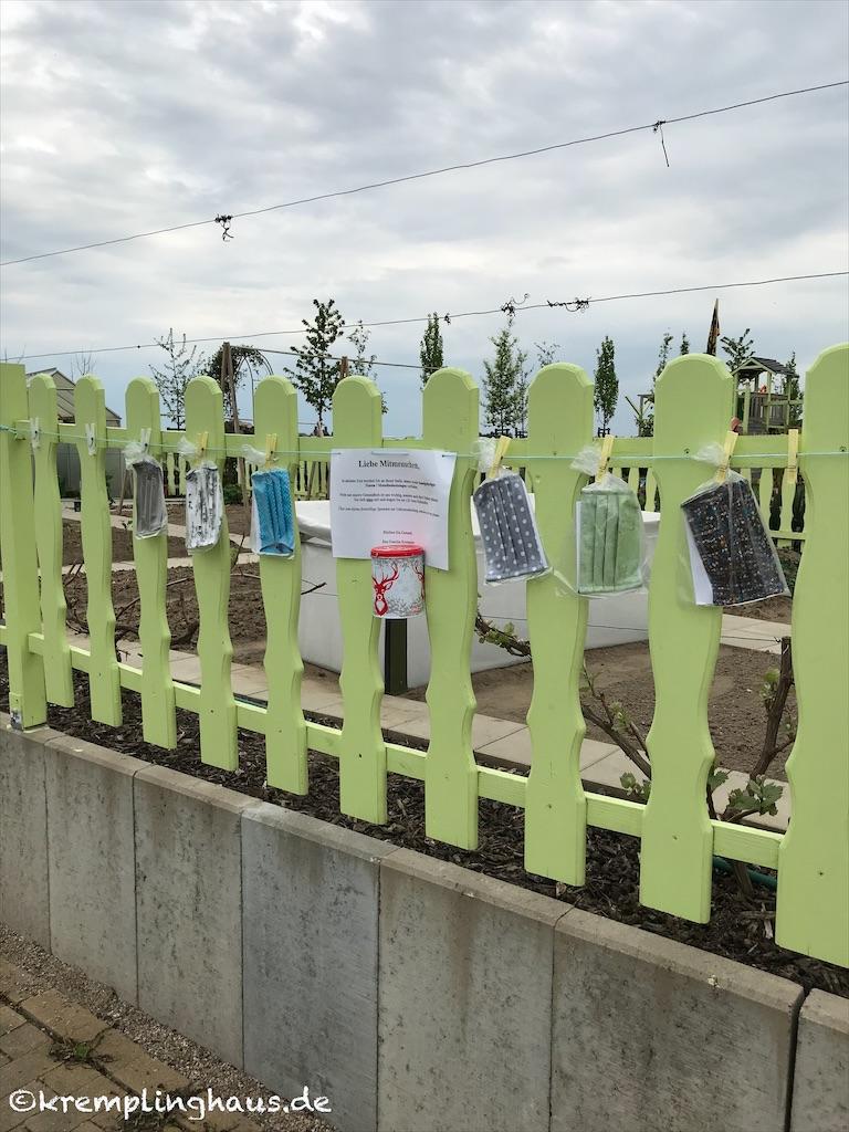 Behelfsmasken am Gartenzaun mit Spendendose
