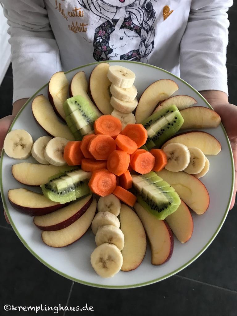 Obstteller mit Apfel, Banane, Kiwi und Möhre
