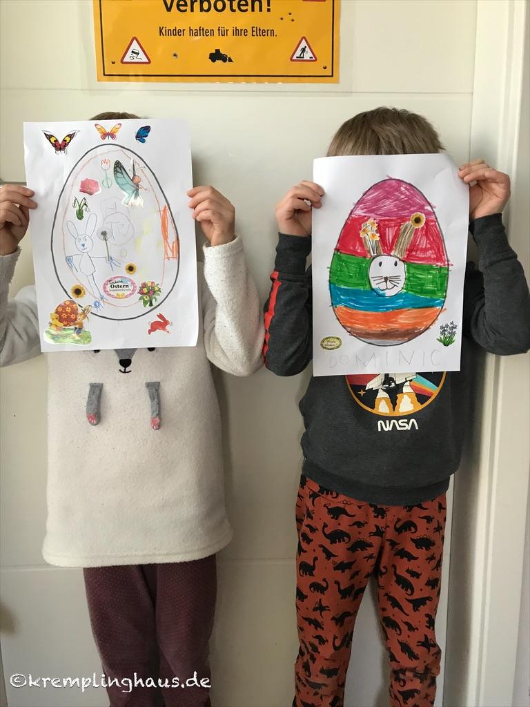 Kinder zeigen ihre gemalten Osterbilder