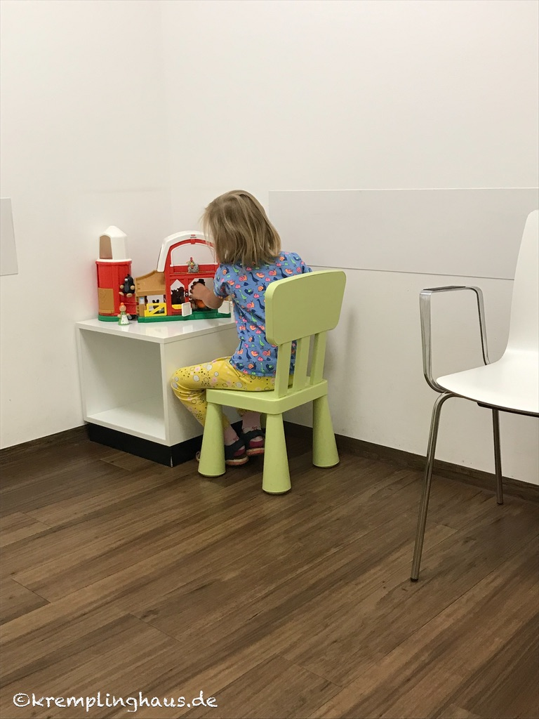 Kind spielt an einem kleinen Tisch mit einem Bauernhofhaus und sitz dabei auf einem grünem Stuhl.