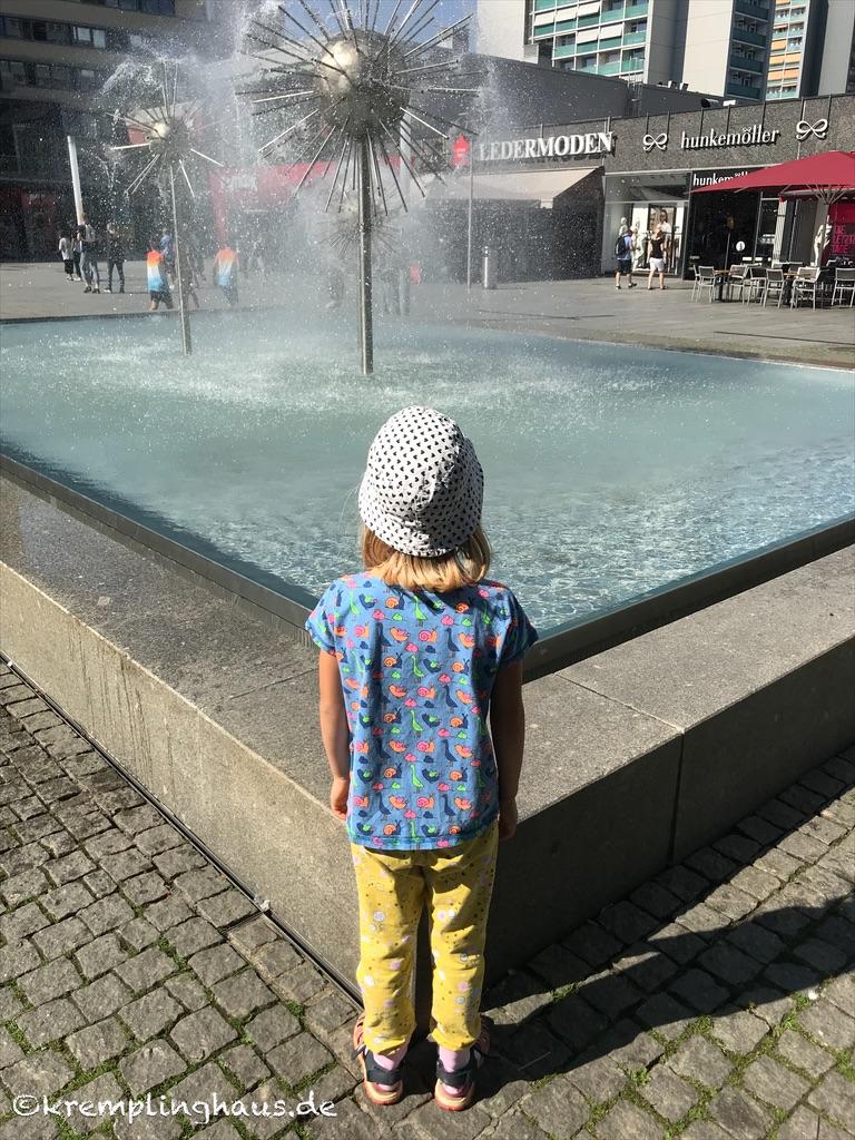 Kind steht vor dem Pusteblumenspringbrunnen auf der Prager Straße in Dresden.