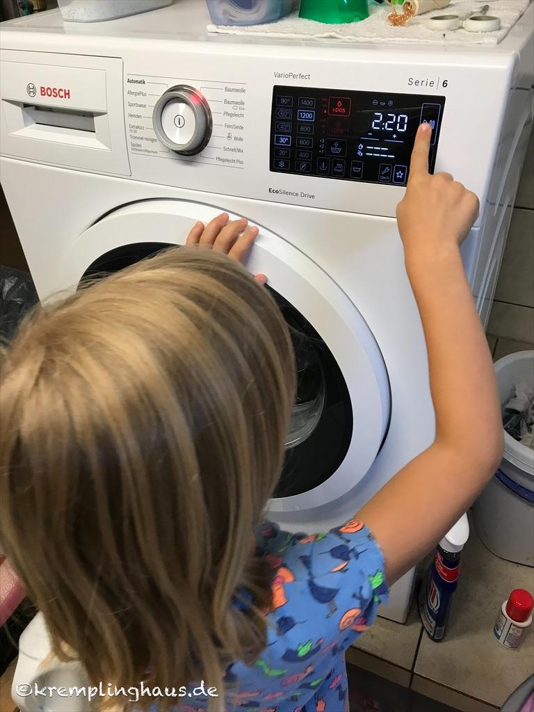 Die Tochter drückt bei der Waschmaschine auf den Startknopf um die se zu Starten.