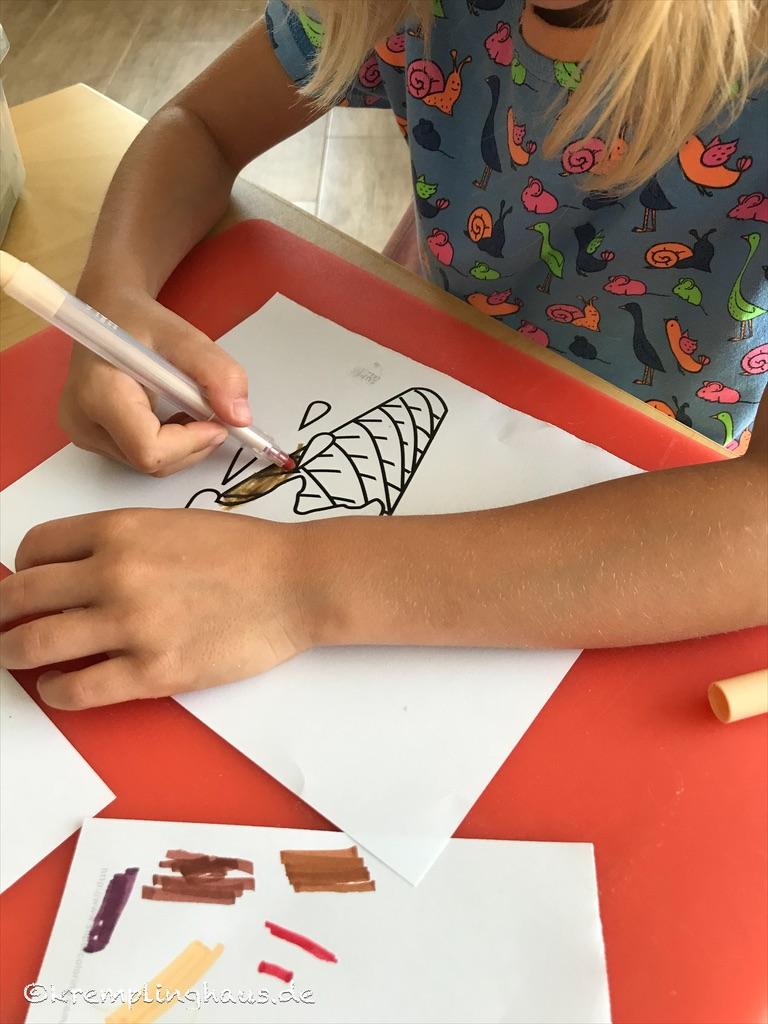 Die Tochter malt ein Bild mit einer Eiswaffel mit Filzstiften aus.