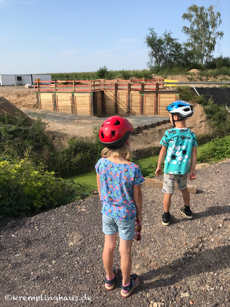 Die Kinder betrachten die Baustelle am Kanal im Dorf .