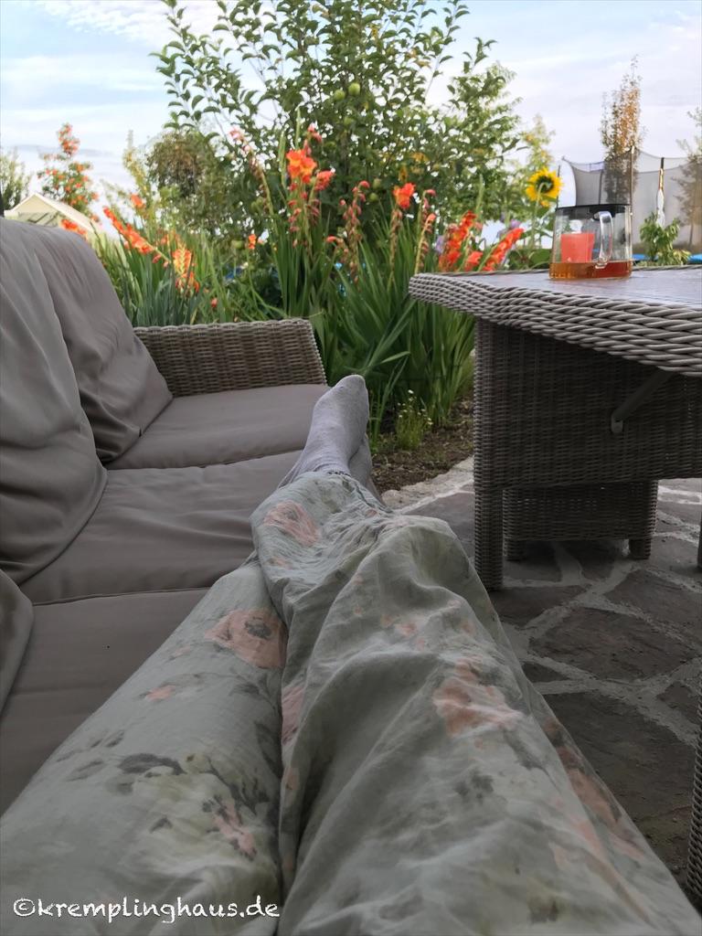 Auf der Gartenbank liegend die Blumen im Garten am Abend beobachten