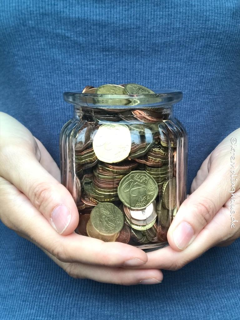 Kleingeldsparen Glas voller Münzen gehalten in 2 Händen