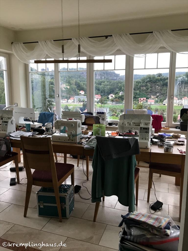 Tisch voll mit Nähmaschinen vor großem Panoramafenster